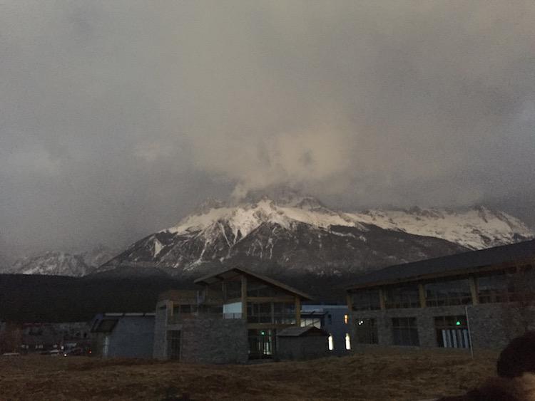 排队等景区内大巴时拍的晨霭中的玉龙雪山
